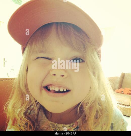 Little girl in a baseball cap winking - Stock Image