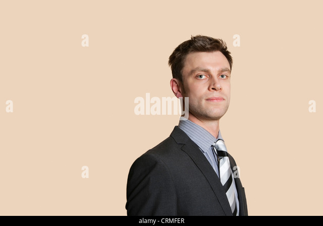 Portrait of a confident mid adult business professional over colored background - Stock Image