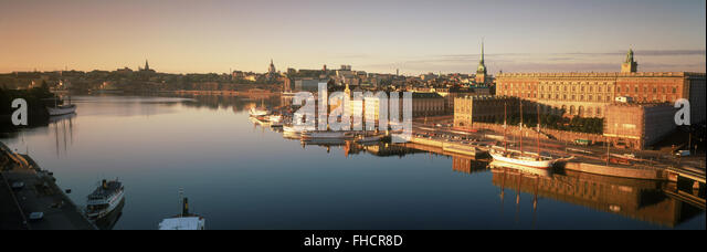 Boats anchored along Skeppsbron at sunrise with Royal Palace and Old Town in Stockholm - Stock Image