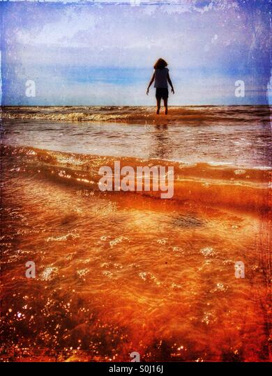 Young girl paddling in the sea - Stock Image
