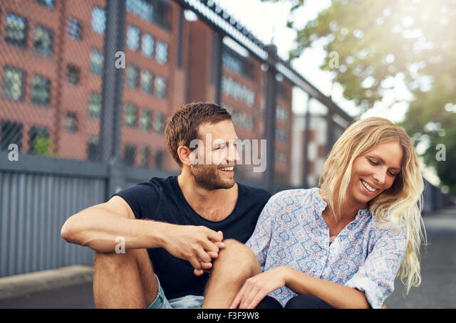 Man teasing his girlfriend, big city couple in a park - Stock Image