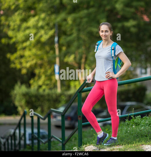 Young sporty girl after a workout stand outdoors. A healthy lifestyle. - Stock Image