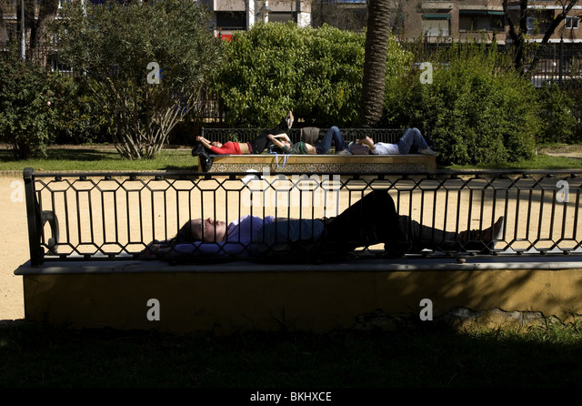Tourists sleep in the benches of the Murillo Gardens in Seville, March 11, Spain, 2008. Photo/Chico Sanchez - Stock Image