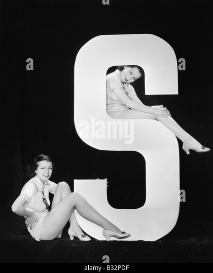 Women posing with huge letter S - Stock Image