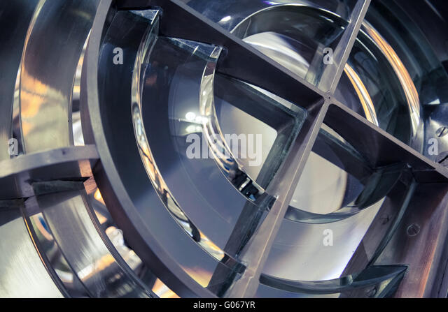 Lighthouse lamp with lens made of glass rings. Close up photo with selective focus and vintage tonal correction - Stock Image