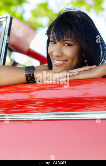 young adult brunette woman leaning on convertible red car and looking at camera. Vertical shape, front view, copy - Stock Image