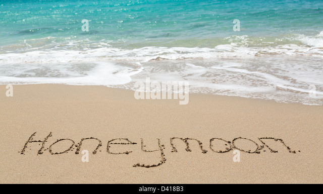 Honeymoon words written into sand on a tropical beach - Stock Image