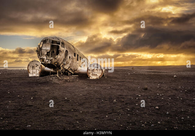 Old crashed plane abandoned on Solheimasandur beach near Vik in Iceland with heavy storm clouds in the sky - Stock Image