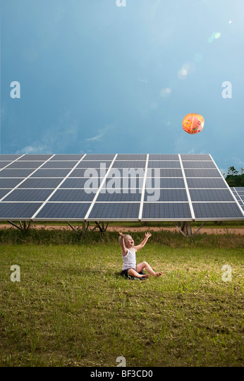 Girl and balloon in front of solar panel - Stock Image