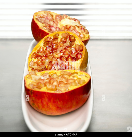 Halved pomegranates in bowl, detail - Stock Image