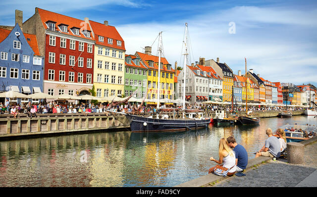 Turists resting at Nyhavn Canal, Copenhagen, Denmark - Stock Image