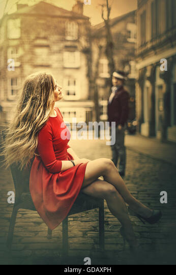 young beautiful blond woman sitting on chair in middle of cobble street - Stock Image