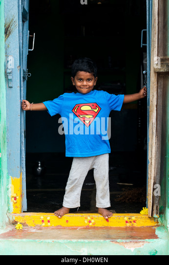 Young Indian boy wearing a superman t shirt standing in the doorway of his home in a rural indian village. Andhra - Stock Image