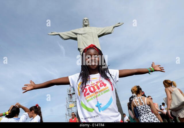 Young woman from Mozambique with her arms outstretched in front of the Christ the Redeemer statue, Cristo Redentor - Stock Image
