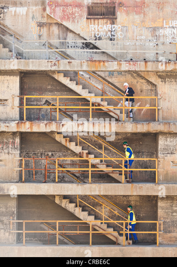 Workers climbing steps on dry dock - Stock Image