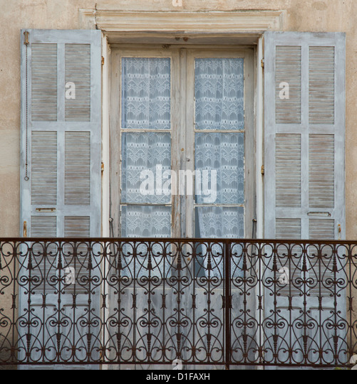 An old window, balcony and curtains in the picturesque village of Aregno in the inland Haute Balagne region, Corsica, - Stock-Bilder