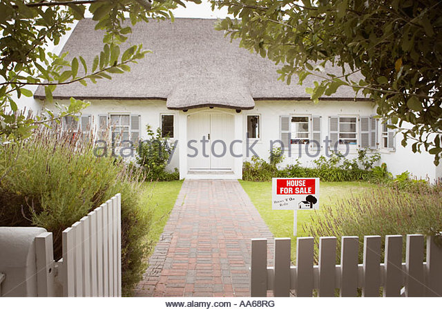 House with for sale sign in yard and open wooden fence - Stock Image