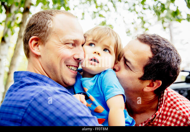 Gay fathers kissing baby son outdoors - Stock Image