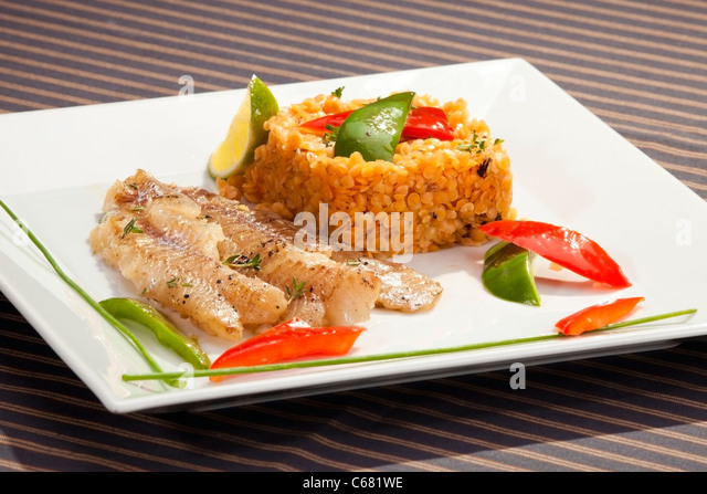 Grilled codfish with red lentil and bell pepper slices - Stock Image