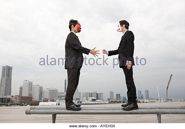 Businessmen wearing masks playing a game - Stock Image