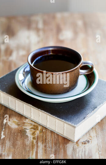 Black coffee and book on wooden table - Stock Image