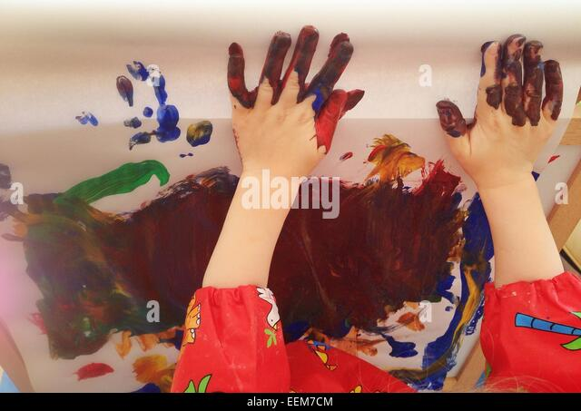 Kid (2-3) painting with hands - Stock Image