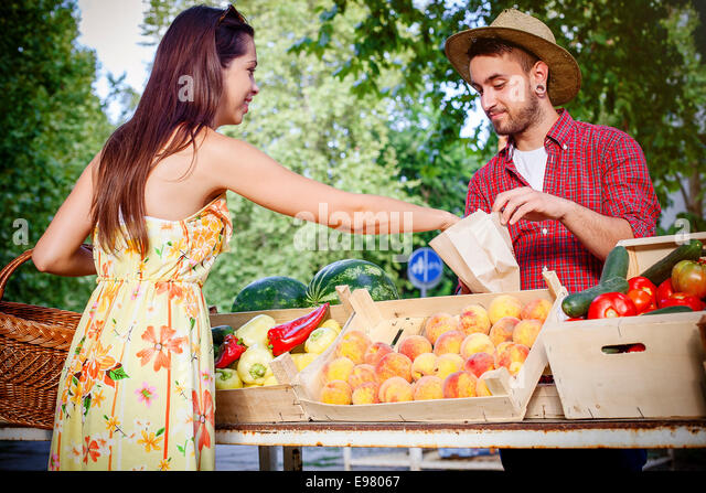 Woman buying fruit at market stall - Stock Image
