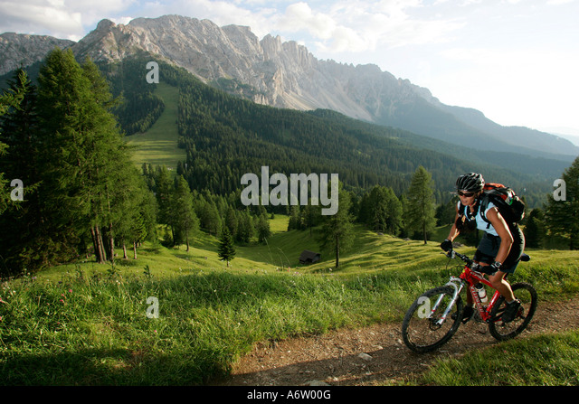 Female mountain biker on the Karer pass, Latemar in the background, Dolomites, Italy - Stock Image