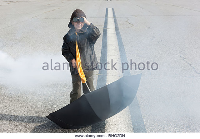 Boy on runway with binoculars and umbrella - Stock Image