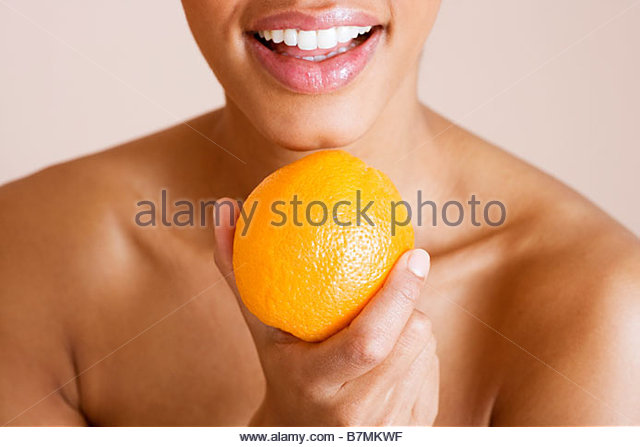 A woman holding an orange - Stock Image