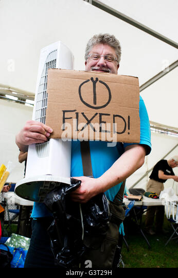 Restart project - repairing electrical equipment .A man holds a repaired fan and a sign saying 'fixed'. - Stock Image