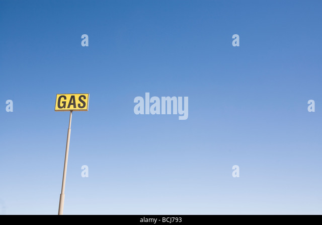Yellow and black GAS sign on tall pole against blue sky Room for type - Stock Image