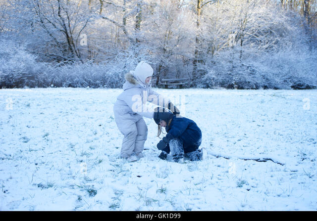 children playing in snow. winter, sibling, frost, forest. - Stock-Bilder