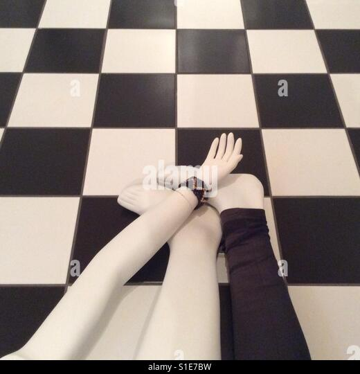 Black and white floor with body parts of a display dummy coming into frame - Stock-Bilder
