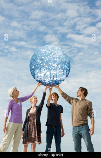 Ecology concept, people holding up planet of water - Stock Image