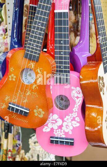 Hawaii Hawaiian Honolulu Waikiki Beach resort market marketplace vendor stall shopping sale display ukuleles - Stock Image