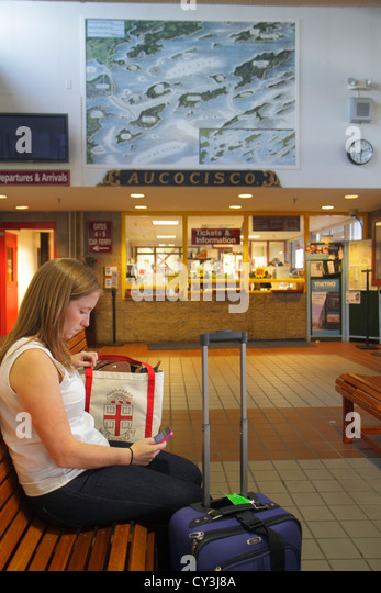 Maine Portland Historic Old Port District Maine State Pier Casco Bay Lines Ferry Terminal woman waiting luggage - Stock Image