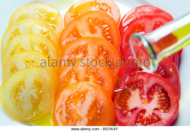 Sliced tomatoes, chopped basil & drizzled olive oil on a plate - Stock-Bilder