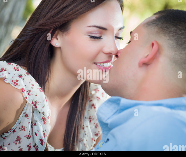 Happy Mixed Race Romantic Couple Kissing in the Park. - Stock-Bilder