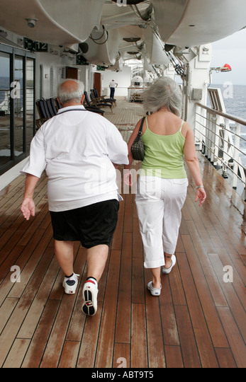 BVI Tortola Holland America Caribbean cruise from New York ms Noordam couple walking exercise Promenade Deck - Stock Image