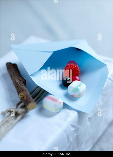 Licorice stick and candies in an envelope - Stock Image