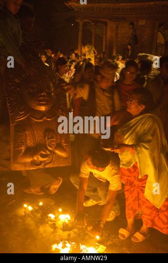 Burning butter lamps smoke and praying people at the chariot of Seto Macchendranath Kathmandu Nepal - Stock Image