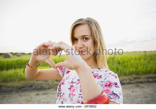 Portrait of beautiful woman making heart sign with hands - Stock Image
