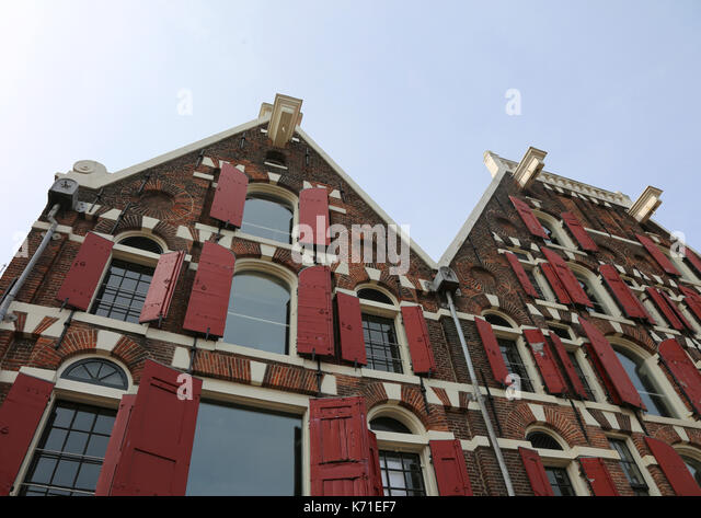 Dutch house facades and under the roof the protruding hook to lift the furniture during removals - Stock Image