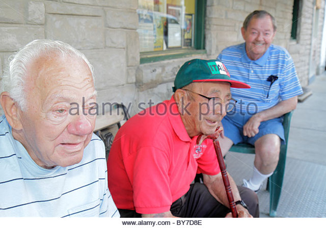 Baltimore Maryland Little Italy ethnic neighborhood community man senior elderly old talking sit on sidewalk interact - Stock Image