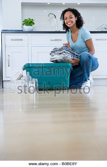 Young woman putting newspaper bundle into recycle bin by glass jars and tin cans, smiling, portrait, ground view - Stock Image