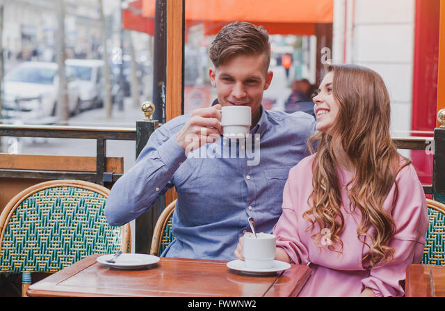 young happy couple drinking coffee and laughing in cafe in Europe, dating, good positive moments - Stock-Bilder