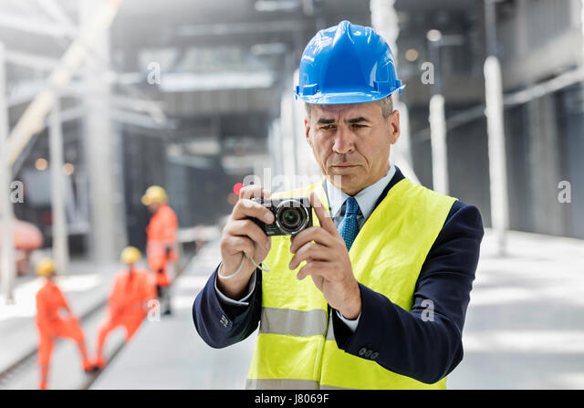 Businessman using digital camera at construction site - Stock-Bilder
