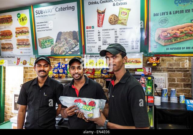 Mumbai India Asian Churchgate Jamshedji Tata Road Subway sandwich shop restaurant man employee coworkers uniform - Stock Image
