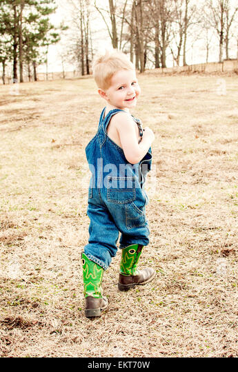 boy in denim coveralls and boots walks in the country - Stock Image